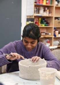 Artist Marisa Owens works on a ceramic piece.