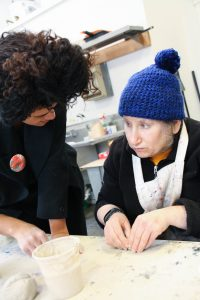 Artist Elizabeth Rogers learns ceramic techniques from Instructor Sharece Phillips.
